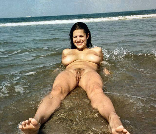 Having fun nude in the splashing ocean waters