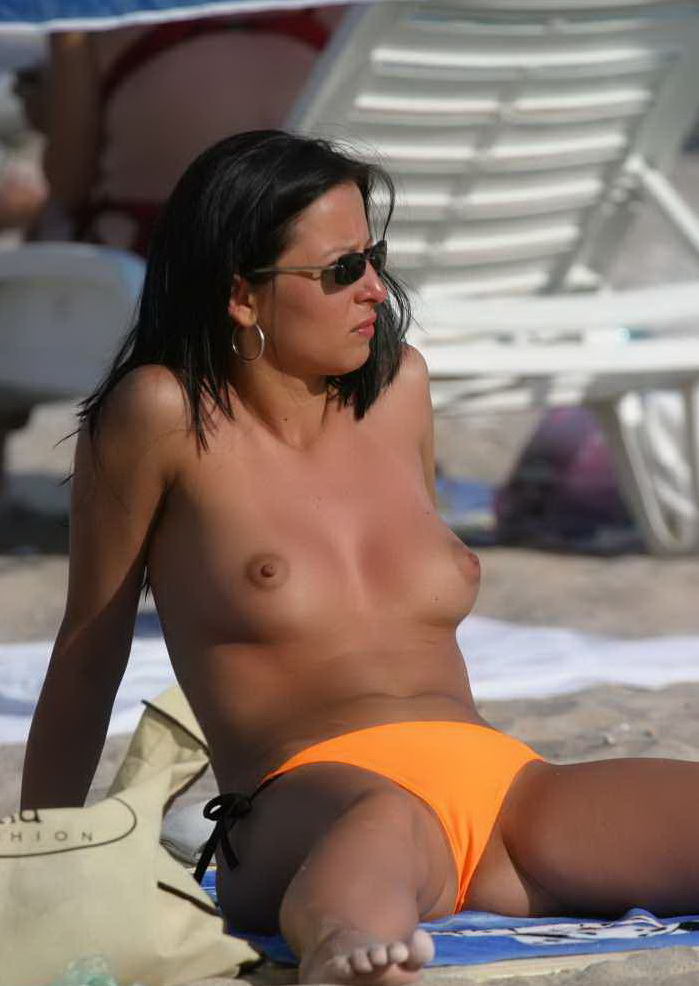 Topless babe sunbathing on nudist beach