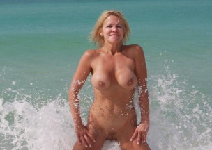 611-Flirty-blonde-splashing-nude-in-the-surf.jpg