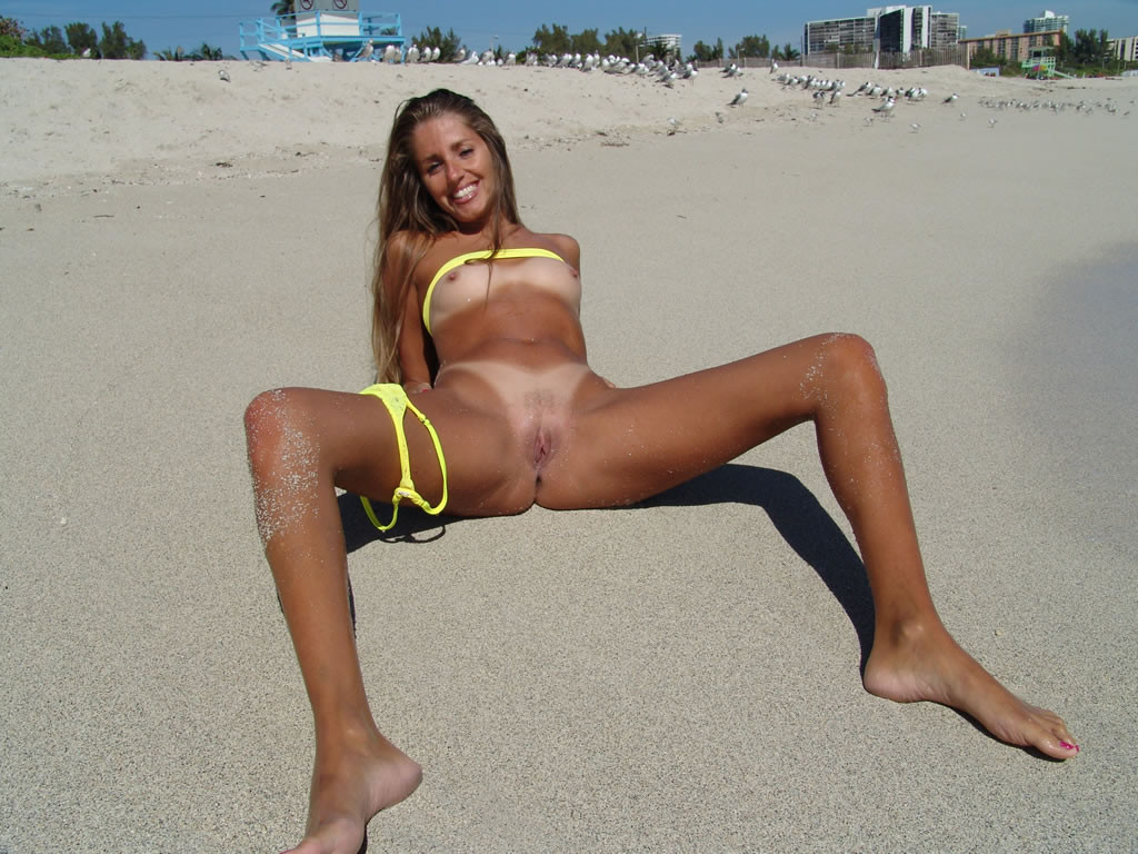 Naked babe exposing her shaved pussy on warm beach