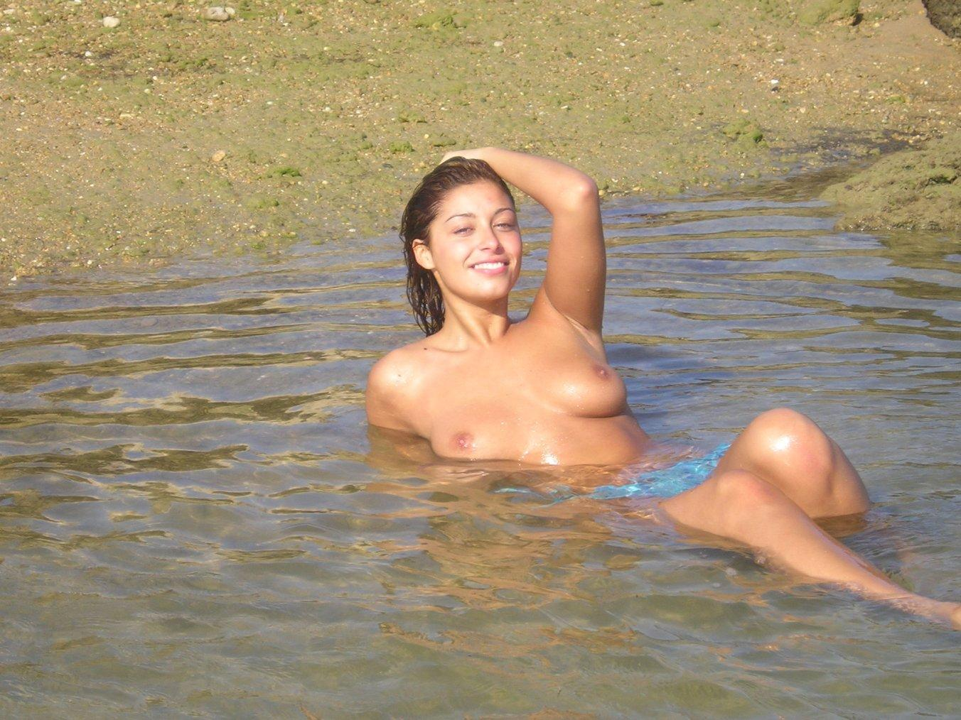 Hot topless brunette laid back in the water