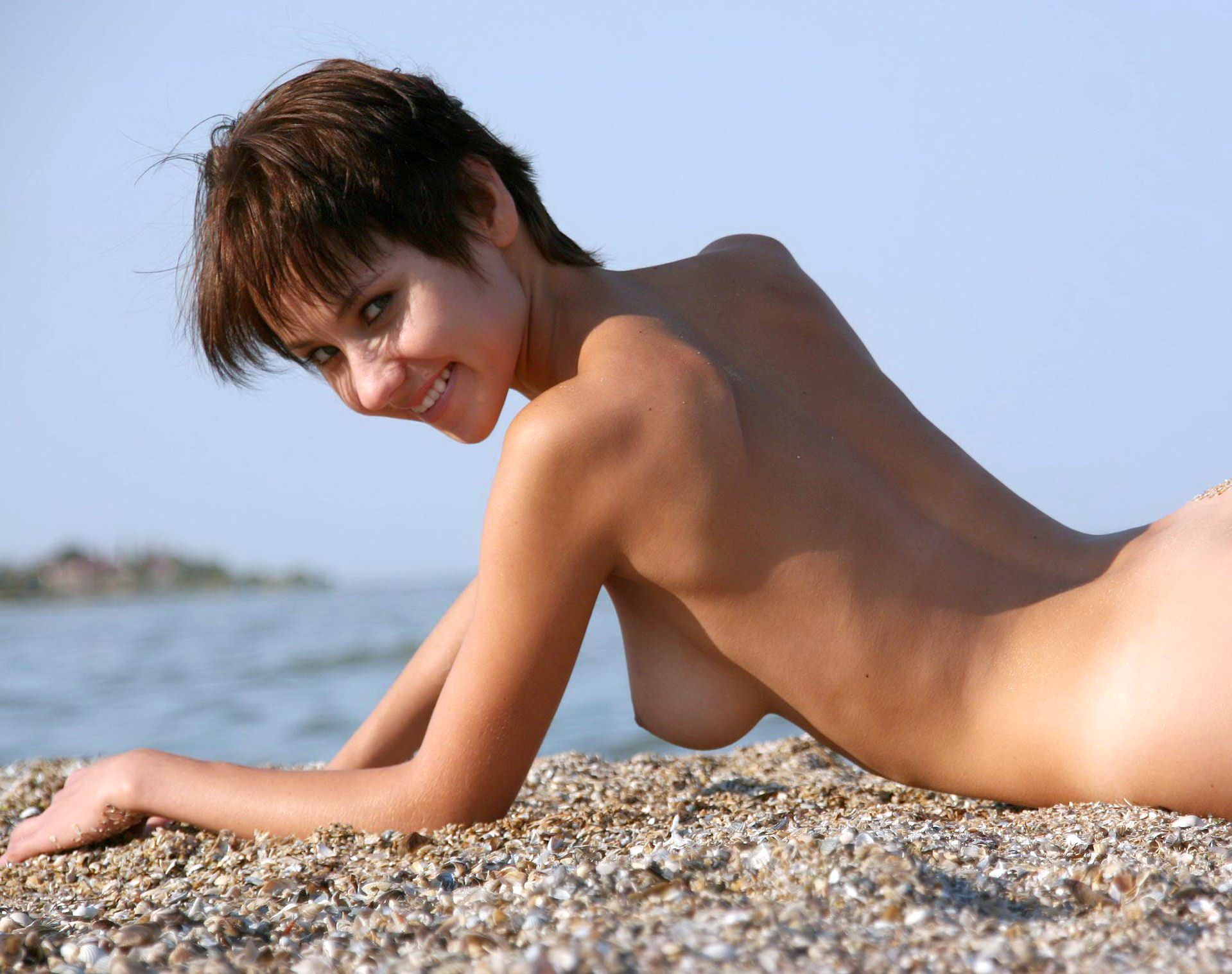Pixie haired cutie posing topless on the beach