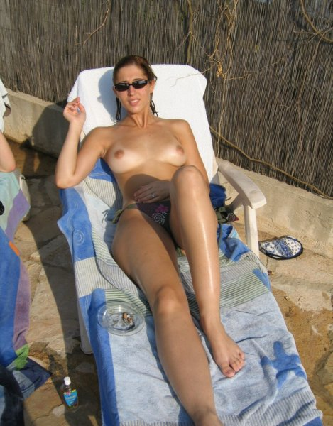 Topless babe suntanning outdoors