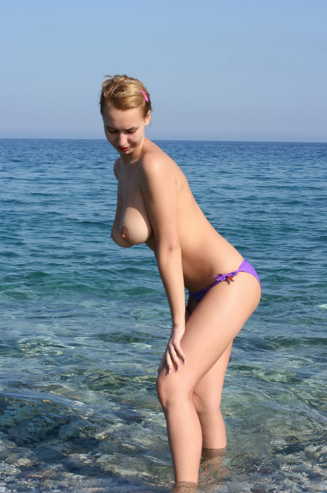 Topless busty girlfriend having fun in the water